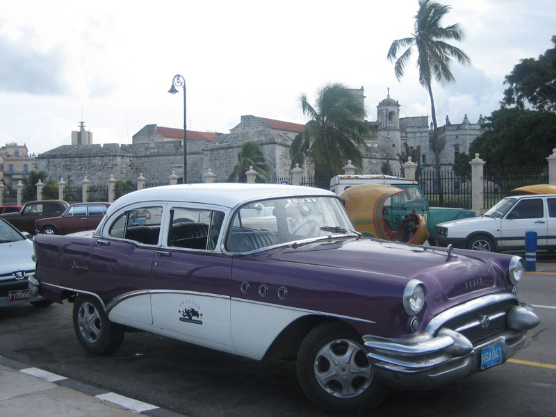 A classic American car from the fifties next to a remaining segment of the old city walls in Havana